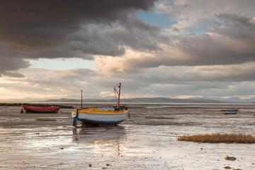 Fishing boats lie on Morecambe beach as evening storm clouds approach
