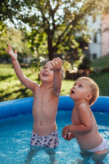 Happy brother and sister standing in the pool