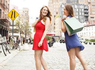 Two women with shopping bags having fun out shopping.