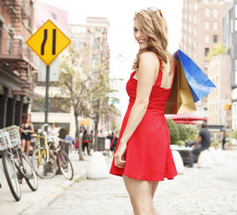 An attractive young woman in a bright red dress with shopping bags over her shoulder smiles at viewer. She is outdoors on a cobblestone city street in New York City.