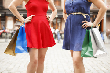 Two women outdoors, hands on hips with shopping bags. Torso detail.