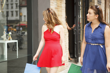 Two women looking into a store window as they walk down the street.