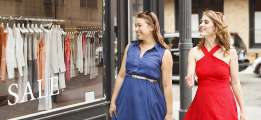 Two happy women looking in a clothing store window with a SALE sign.