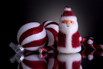 Christmas decorations fluffy santa 2 candy canes and 2 balls red and white shot front on on a grey background