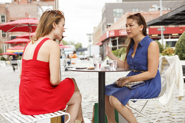Two women sitting, chatting at an outdoor table.