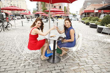 Friends sitting at an outdoor table raising drinks and toasting to viewer.