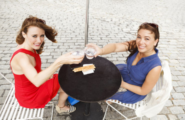 Friends sitting at an outdoor table looking up and and toasting to viewer.