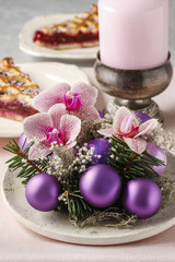 Woman making christmas decorations with violet balls, fir and or