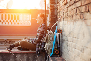 Brave smiling traveler man sitting on the edge of the roof and listening music in earphones with backpack and skateboard (intentional sun glare)