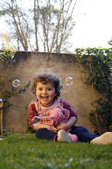 Girl child looking soap bubbles