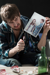 Heartbroken guy destroying love photos