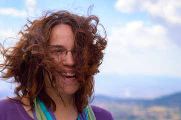 Excited young woman with wind blown hair outdoors