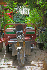 motor tricycle against background of the garden
