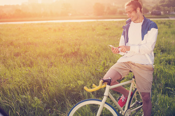 young man with bicycle in green field looking at smartphone at sunset (intentional sun glare and vintage colors)