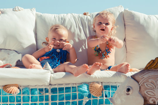 Happy children on the background of the sea. Funny kids playing outdoors. Summer vacation concept