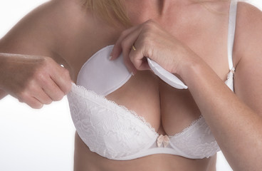 Woman boosting her bra size with some added padding