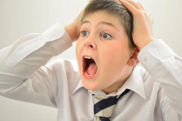 Teen boy screaming holding his hands behind  head