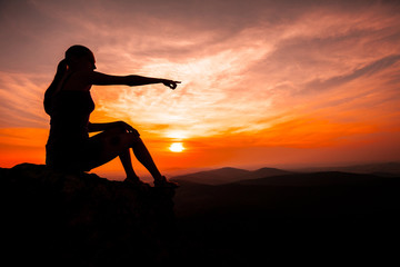 Silhouette of woman watching sunset and pointing