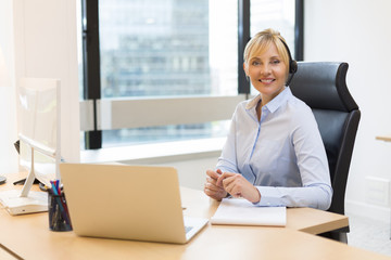 Attractive Business woman working on laptop. Headset. Building b
