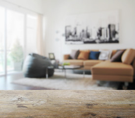 wooden table top with blur of modern living room interior as bac