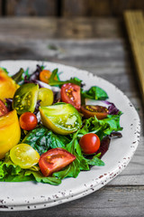 Fresh salad with spinach,arugula and heirloom tomatoes on rustic
