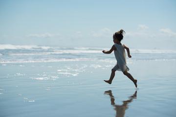 波打ち際を走る少女のシルエット
