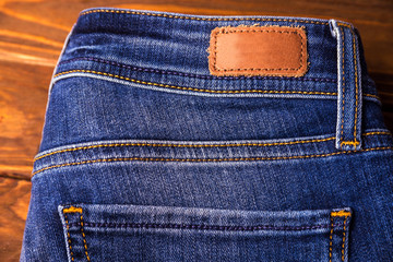 Blue jeans with half of back pocket and brown leather tag