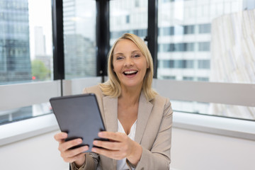 Happy Middle aged business woman using digital tablet. Modern office
