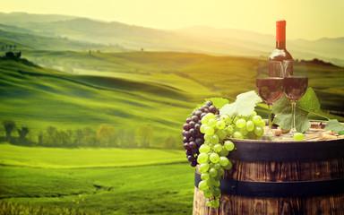 Fototapete - Red wine bottle and wine glass on wodden barrel. Beautiful Tusca