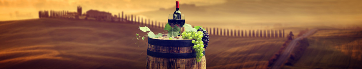 Wall Mural - Red wine bottle and wine glass on wodden barrel. Beautiful Tusca