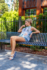 Cute sexy woman in summer clothing sitting on iron bench.