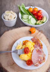 Breakfast: scrambled egg and bacon with salads, vegetables and banana on a dark wooden table, selective focus