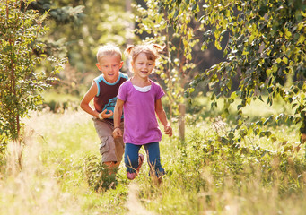 Little girl and boy playing together in sunny summer garden