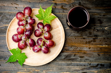 Red grape and juice on wooden background