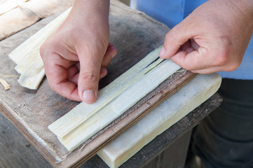 The working of Papyrus in Syracuse: an artisan is superimposing perpendicular thin strips obtained fom the stem of the plant to make a new leaf