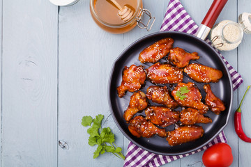 Baked chicken wings in honey sauce sprinkled with sesame seeds.