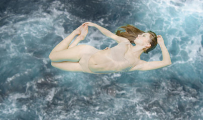 Beautiful woman floating in swimsuit on blue stormy underwater