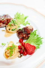 Duck meat with berries and ravioli