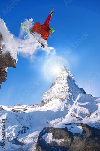 Wall mural Snowboarder jumping against Matterhorn peak in Switzerland