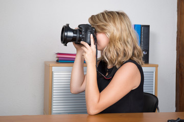 Photographer woman girl is holding a camera taking photographs