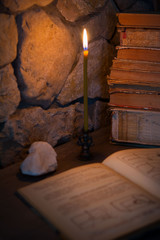 Burning wax candle and old books, selective focus