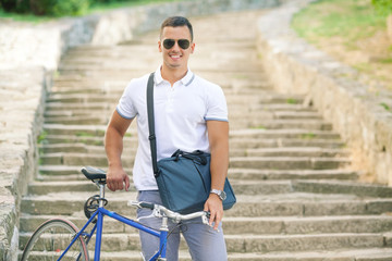 Smiling young cyclist holding his bicycle while going down the stairs in the old town