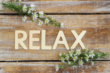 Relax written on rustic wood and chamomile flowers
