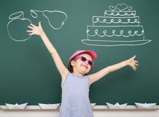 girl drawing cake and fruit on school board