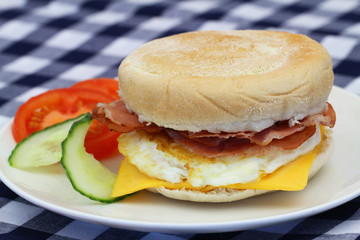 Egg and bacon muffin on white plate, closeup
