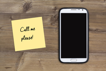 call me please message, smart phone and sticky note on wood - top view