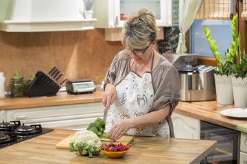 Mature woman cutting vegetable in the kitchen.