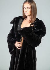 Elegant woman in long mink fur cout is looking at camera.