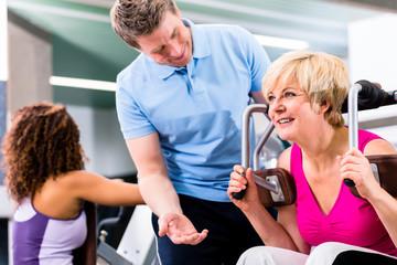Seniorin beim Training im Fitnessstudio mit Trainer