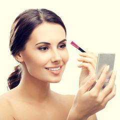 woman with cosmetics brush and mirror